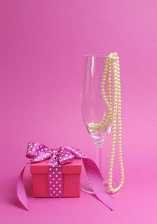 Pretty Pink And Feminine Gift With Polka Dot Pink Ribbon And A Champagne Glass With Pearls Royalty Free Stock Image