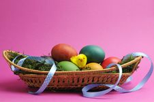 Rainbow Color Easter Eggs In Wicker Basket Against A Pink Background. Royalty Free Stock Photo