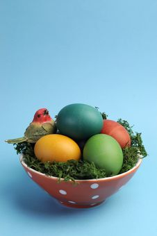 Easter Still Life With Rainbow Color Eggs In Orange Polka Dot Bowl Against A Blue Background. Stock Photo