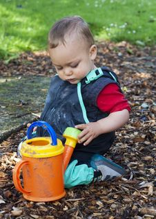 Child Playing With Watering Can Royalty Free Stock Photos