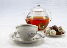 Cup On A Saucer, Teapot And Chocolates Stock Photo