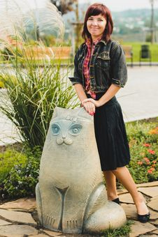 Young Woman Standing Near Funny Cat Statue Royalty Free Stock Images