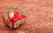 Egg Swollen By A Red Bow Lies In The Nest Royalty Free Stock Images