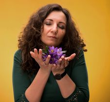 Curly Woman Smelling Crocus Flowers With Close Eyes