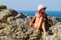 Free Girl In Glasses Sitting On The Rocks By The Sea Stock Photos - 29627563
