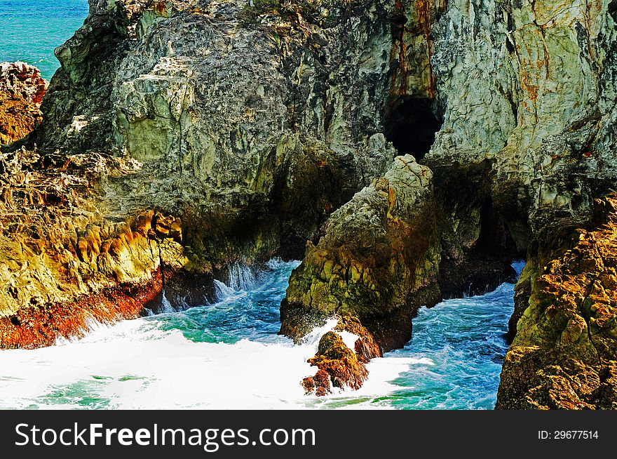 Rugged rocks & caves of tropical island cliff