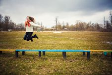 The Girl In A Orange Scarf Jumping Over Bench Royalty Free Stock Photo