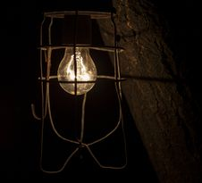 Old Dirty Glowing Bulb. On Black Background. Royalty Free Stock Photo