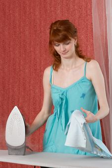 The Young Woman Irons Clothes Royalty Free Stock Photography