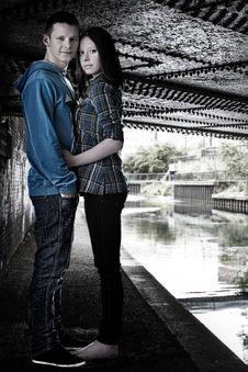 Young Cute Couple Hugging Under The Bridge Stock Photos