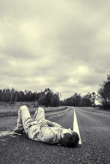 Young Guy Lies On The Road Royalty Free Stock Photo