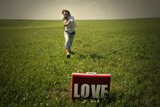 Free Guy In The Field Looks In Suitcase With The Word Love Stock Images - 29870094