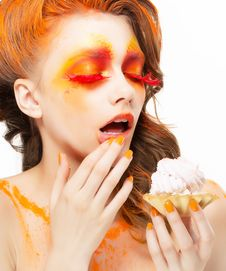 Gilding. Tempting Woman Eating A Pie With Cream. Bright Red-Golden Makeup Stock Image