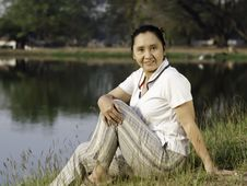 Woman Sitting On Green Field By Lake Royalty Free Stock Photo