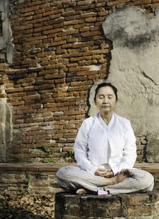Woman Meditating In Temple Stock Photo