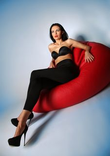 Free Sexy Brunette Beauty Sitting On A Red Armchair Royalty Free Stock Photography - 29951757
