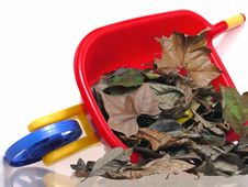 Toys: Plastic Wheelbarrel And Dry Leaves Royalty Free Stock Photography
