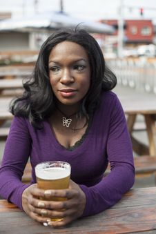 Free Young African American Woman Drinks Pint Of Pale Ale Stock Photo - 30165640