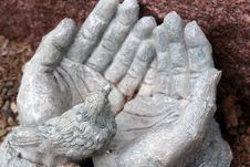 Stone Hands Open And Holding Little Bird In Palm Stock Images