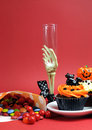 Free Halloween Cupcakes, Skeleton Glass And Candy Treats On Red Background - Vertical. Stock Images - 30399664