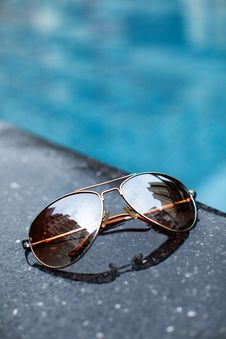 Sunglasses  By A Blue Pool In City Town Stock Photo