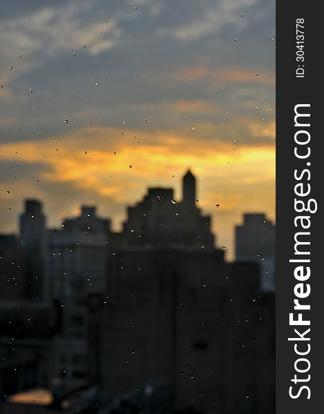 Rain drops at window with unfocused Manhattan skyline
