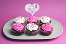 Pink Ribbon Day Message Across White Heart Toppers On Pink And White Decorated Red Velvet Cupcakes Royalty Free Stock Photos