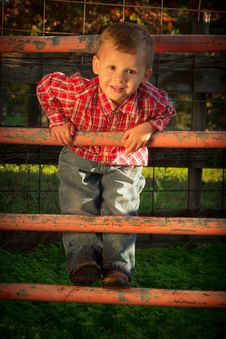 Free A Smiling Young Boy Climbs Corral Fence Royalty Free Stock Photos - 30588678