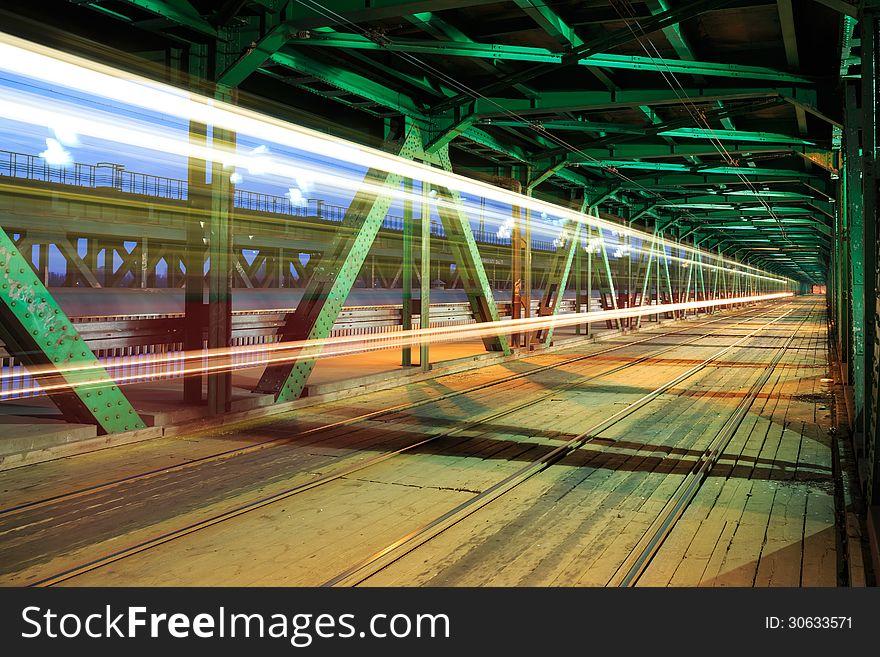 Tram in traffic on the bridge at night
