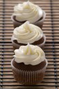 Free Three Chocolate Cupcakes With Vanilla Frosting In A Row Royalty Free Stock Image - 30641176
