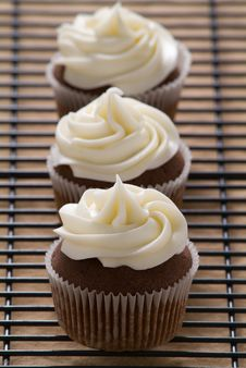 Three Chocolate Cupcakes With Vanilla Frosting In A Row Royalty Free Stock Image