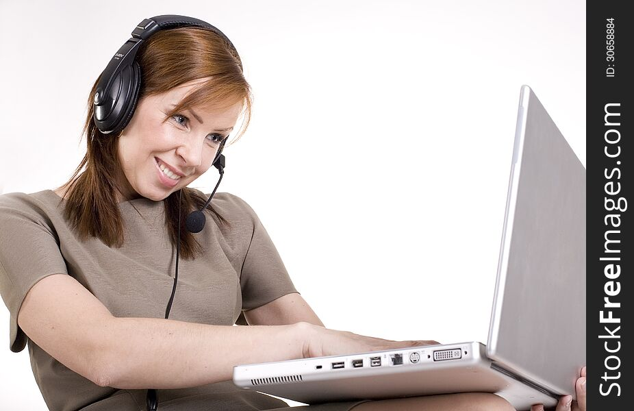 Portrait of pretty call operator smiling and typing on lap top
