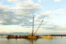 Crane At Construction Site On River Stock Image