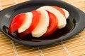 Free Tomato And Mozzarella On Black Dish At Bamboo Royalty Free Stock Photo - 30822705