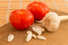 A Few Cloves Of Garlic With Tomato On The Table Stock Photography