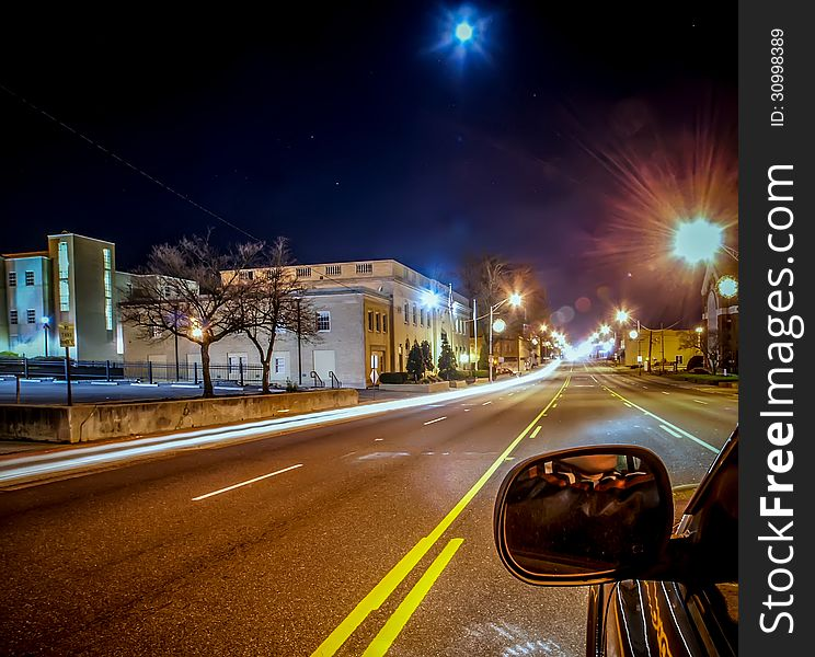 Standing in car on side of the road at night