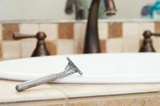 Razor Resting On Edge Of Sink In Bathroom Royalty Free Stock Image