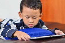 A Boy Playing A Game On Computer Tablet Stock Photography