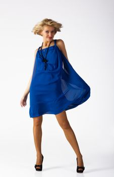 Attractive Young Woman In A Blue Dress Standing In The Studio Stock Photography