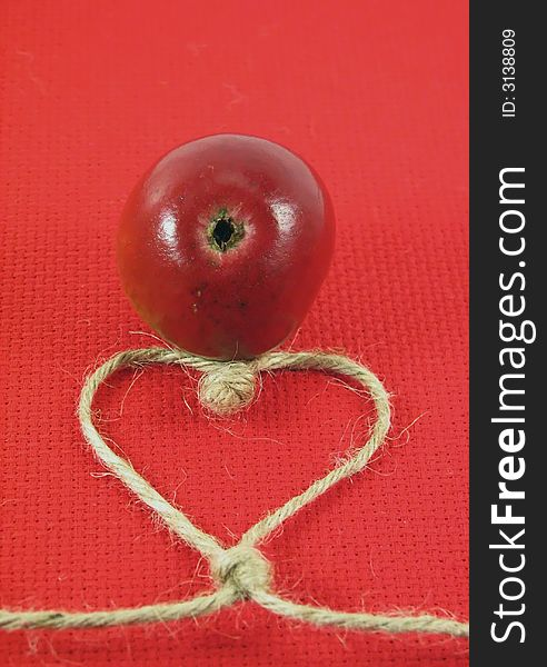 Red apple and string in form o