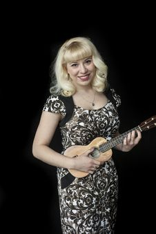 Beautiful Young Woman With Blond Hair Playing Ukulele Royalty Free Stock Photos