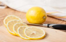 Free Sliced lemon On A Wooden Surface, Knife And Lemon Royalty Free Stock Photos - 31590368