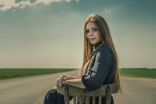 Free Beautiful Girl With Long Hair Sits Outdoors On A Chair On The Road Royalty Free Stock Images - 31625829