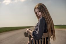 Free Beautiful Girl With Long Hair Sits Outdoors On A Chair On The Road Stock Photography - 31625882