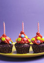 Free Three Bright Candy Covered Cupcakes With Birthday Candles - Vertical Stock Photo - 31700800