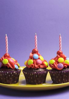 Three Bright Candy Covered Cupcakes With Birthday Candles - Vertical Stock Photo