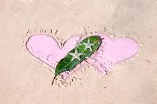 Drawn Hearts And Starfishes On Wet Sand Royalty Free Stock Photos