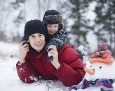 Happy Father With His Son Outside With Snowman Stock Images