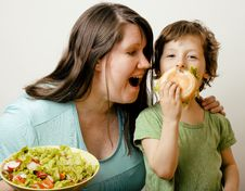 Fat Woman Holding Salad And Little Cute Boy With Hamburger Royalty Free Stock Photo