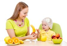 Mother Feeding Little Girl With Healthy Food Sitting At Table